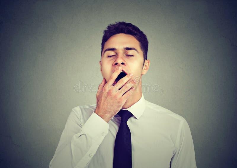 O homem sonolento que boceja com cede a boca foto de stock