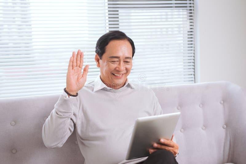 O homem superior asiático com o computador do PC da tabuleta faz a chamada video imagem de stock