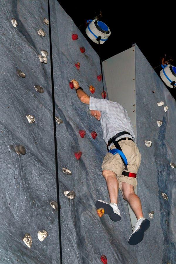 O homem superior com cabelo branco escala a parede da rocha na roupa ocasional ele imagem de stock royalty free