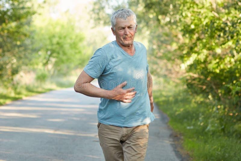 O homem superior considerável atlético cobre o corredor longo do distnace, tem a dor no estômago, prepara-se para a maratona entr fotos de stock