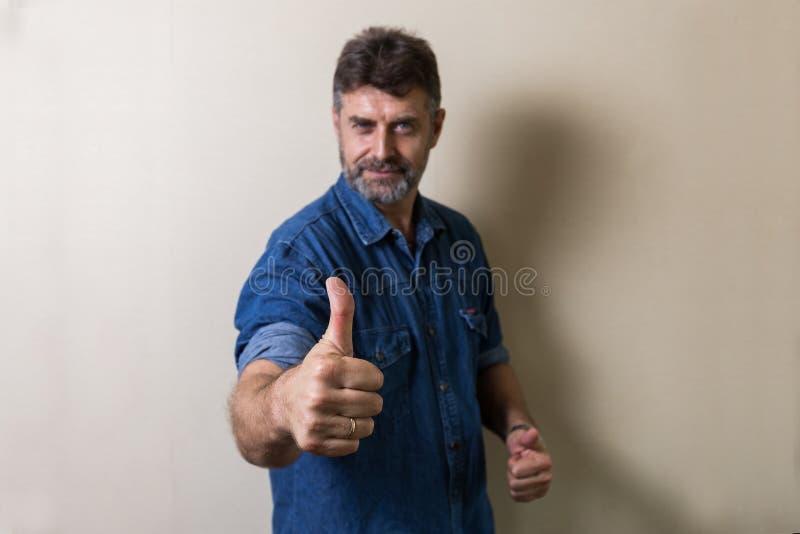 O homem superior dos Caucasians faz os polegares acima foto de stock royalty free