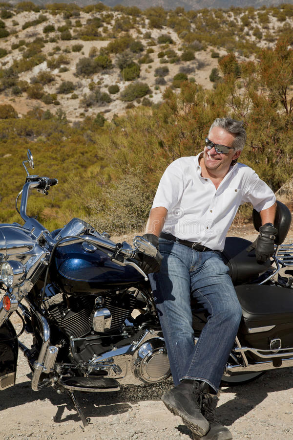 O homem superior inclina-se na motocicleta no deserto foto de stock royalty free