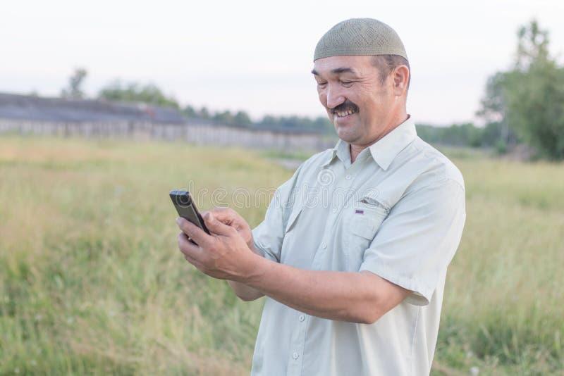 O homem superior muçulmano usa um telefone celular imagens de stock royalty free