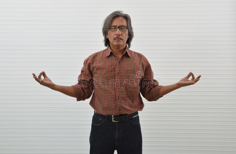 O homem superior na camisa, na calças de ganga vermelha e nos monóculos ocasionais meditando na pose dos lótus, olhos fechou-s fotos de stock