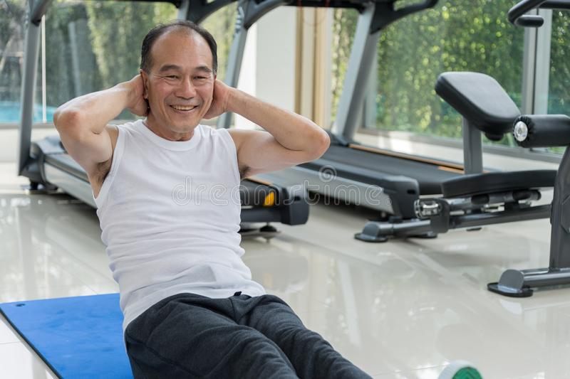 O homem superior que exercita fazendo senta-se levanta no centro de aptidão foto de stock royalty free