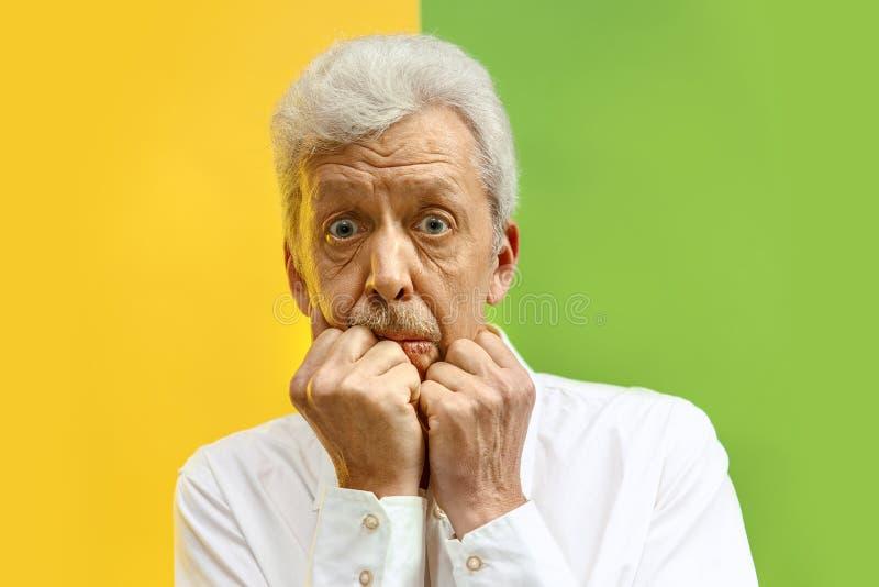 O homem superior que olha surpreendido isolou-se no fundo do estúdio da cor fotos de stock