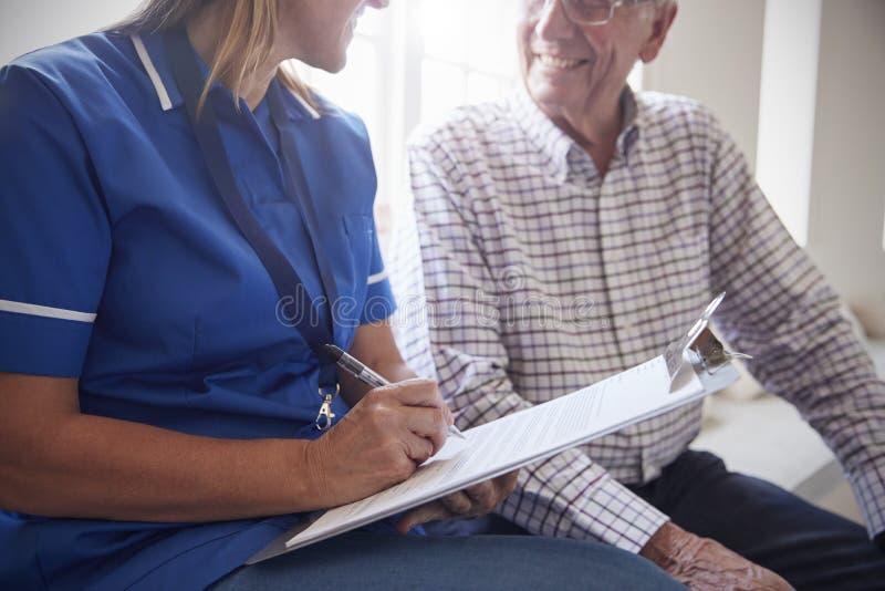 O homem superior senta-se com a enfermeira que faz anotações no lar de idosos imagens de stock royalty free