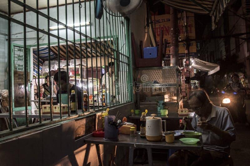O homem superior vietnamiano está comendo uma sopa de macarronete em um restaurante em uma rua de Ho Chi Minh City, Vietname imagens de stock