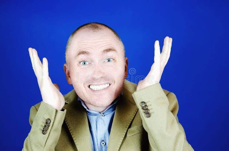 O homem surpreendido em um revestimento de creme joga acima suas m?os para os lados em um fundo azul Lugar vazio para sua propaga fotografia de stock