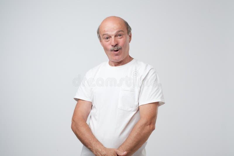 O homem surpreendido emocional superior que está com abriu uma boca pequena fotografia de stock