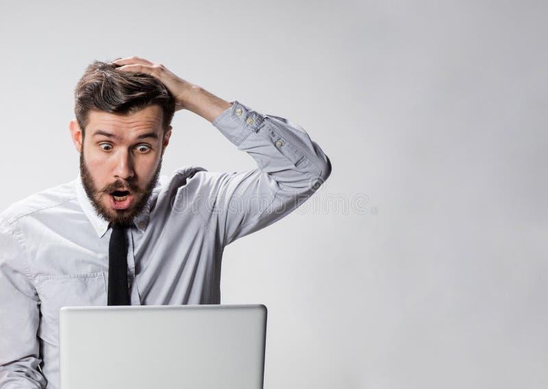 O homem surpreendido jovens com seu laptop foto de stock