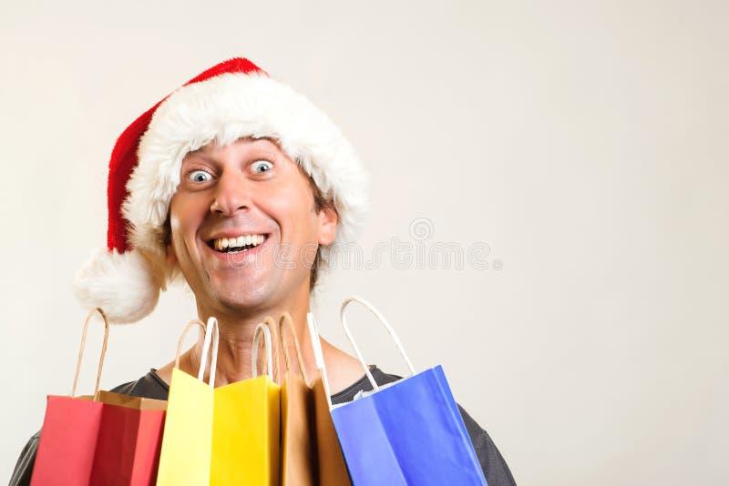 O homem surpreendido no chapéu do Natal guarda os sacos de compras, isolados no branco Compra do Natal e conceito das vendas Disc imagem de stock royalty free