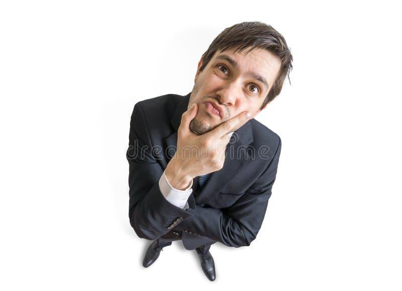 O homem suspeito ou cético novo está olhando-o Vista da parte superior Isolado no fundo branco foto de stock