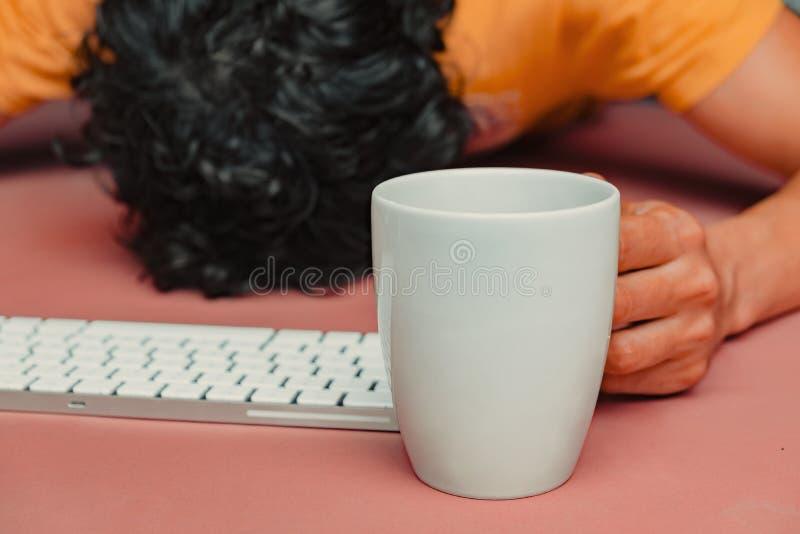 O homem tem queima-se no trabalho Cabeça, teclado, telefone esperto e café fotos de stock royalty free