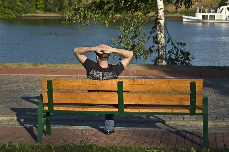 O homem tem um descanso no banco de rio imagens de stock royalty free