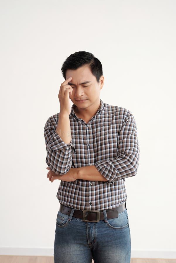 O homem tem uma dor de cabeça imagens de stock