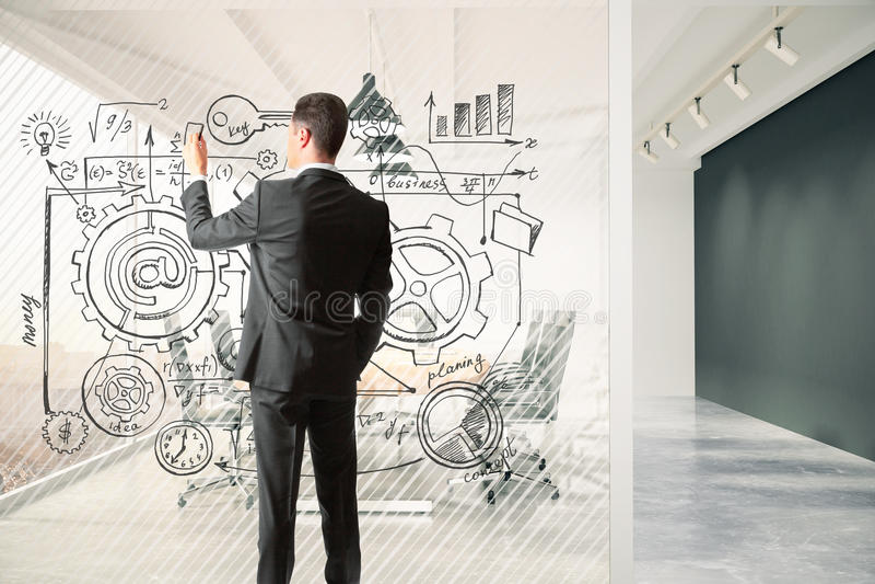 O homem tira o plano de negócios em uma separação de vidro na sala de reunião foto de stock royalty free