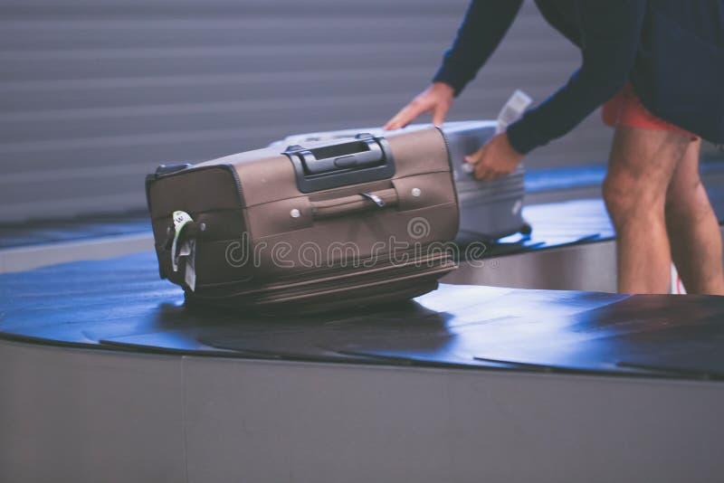 O homem toma a bagagem no salão da chegada do transporte da fita fotos de stock