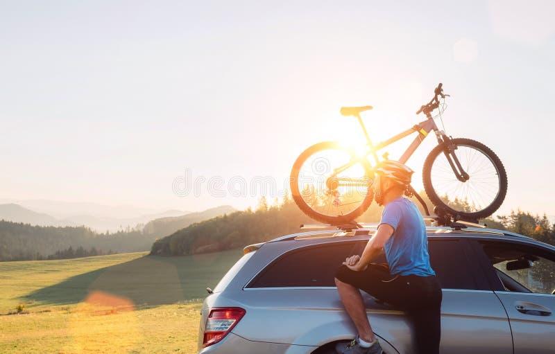 O homem toma sua bicicleta do telhado do carro Conceito biking da montanha fotografia de stock