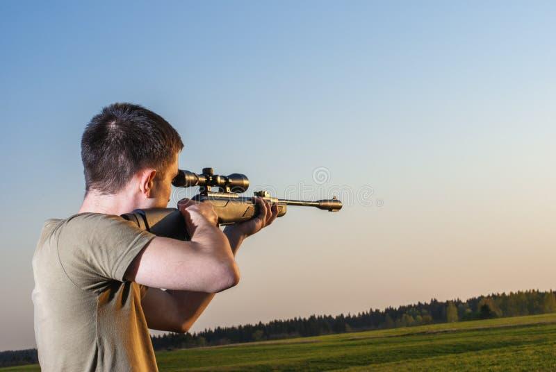 O homem tomou o alvo com seu rifle de atirador furtivo foto de stock
