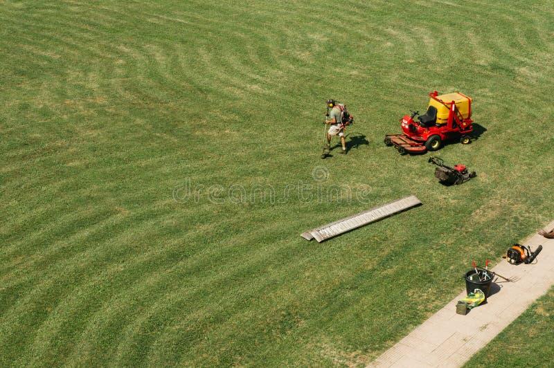 O homem trabalha com o cortador de grama no campo largo Fundo da vista superior imagens de stock royalty free
