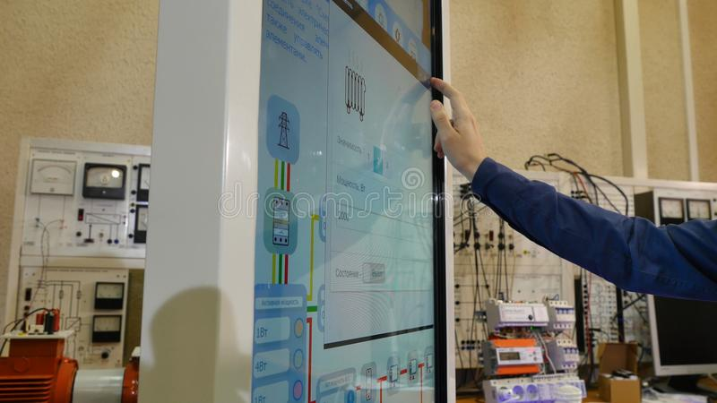 O homem trabalha em um tela táctil O cientista novo usa um grande tela táctil para trabalhar fotografia de stock royalty free