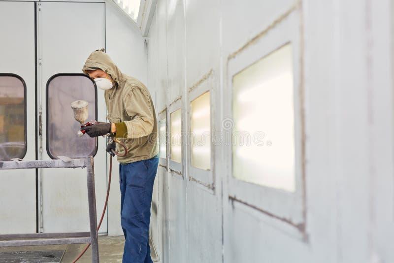 O homem trabalha na cabine da pintura com pistola, pintando detalhes do carro fotos de stock royalty free