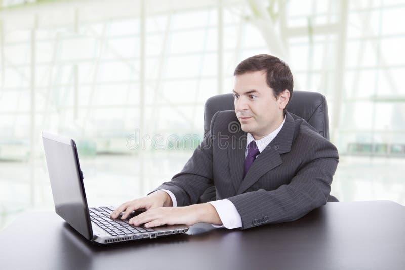 O homem trabalhando com seu laptop fotografia de stock royalty free
