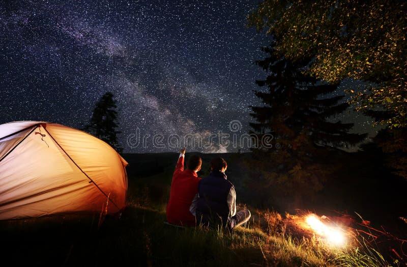 O homem traseiro da vista mostra a fêmea acima em nivelar o céu estrelado na Via Látea perto da barraca e da fogueira em montanha imagem de stock royalty free