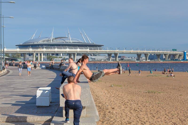 O homem treinam o parkour e freerunning novos na praia do parque da cidade foto de stock