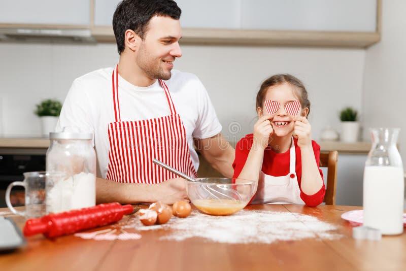 O homem triguenho alegre veste olhares do avental na criança feliz que cobre os olhos com os corações, senta-se na mesa de cozinh imagens de stock