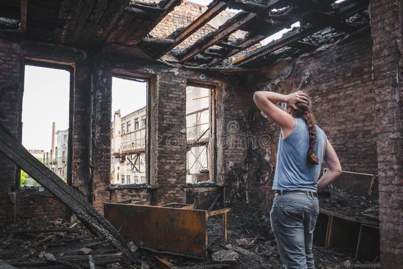 O homem triste guarda sua cabeça à mão e o grito no queimado para fora abriga após o desastre, consequências do fogo fotos de stock royalty free