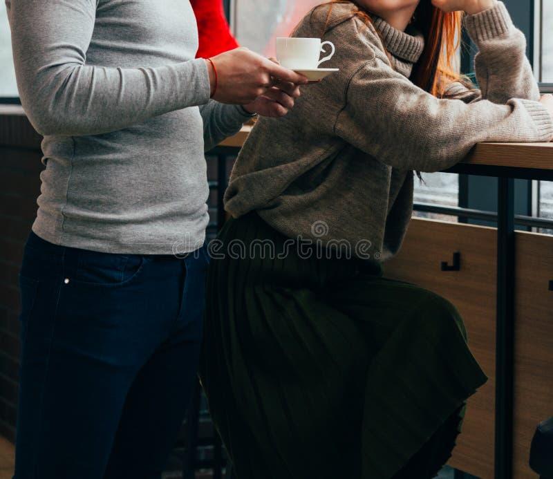 o homem trouxe o café, chá à menina que se senta na tabela fotografia de stock royalty free