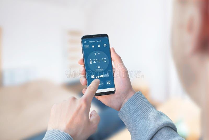 O homem usa o app para controlar o clima na sala de visitas fotos de stock royalty free