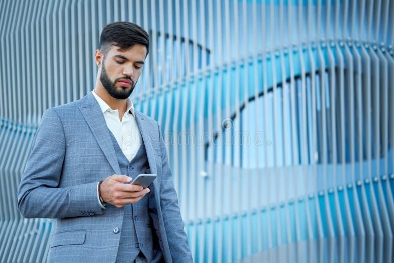 O homem usa um smartphone Homem de negócio profissional urbano do homem de negócios que usa o telefone celular Revestimento vesti imagens de stock royalty free