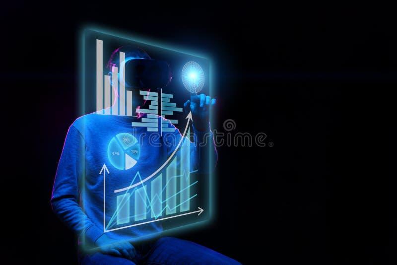 O homem usa uns auriculares da realidade virtual para trabalhar com dados sob a forma dos gráficos e das cartas fotos de stock royalty free
