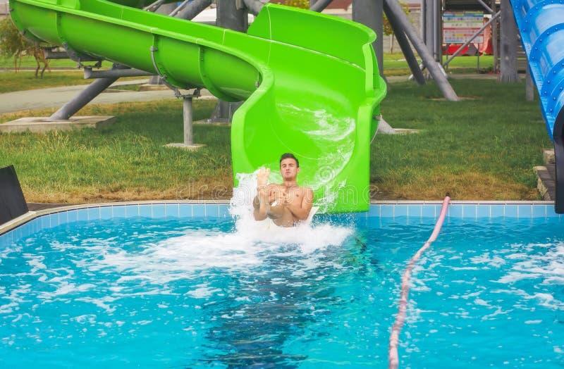 O homem vai para baixo da corrediça de água à piscina no parque imagens de stock royalty free
