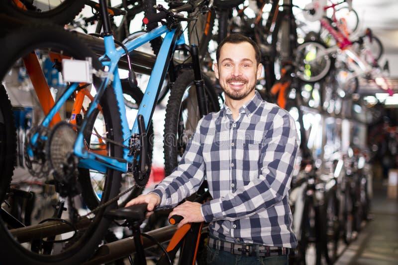 O homem verifica a sela da bicicleta imagens de stock