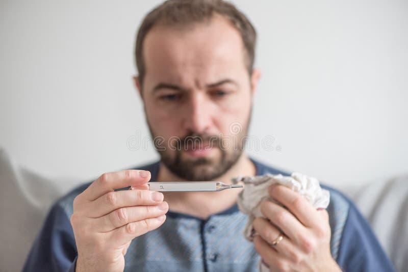 O homem verifica a temperatura corporal com um termômetro de mercúrio Tema de doenças virais, gripe, frios fotografia de stock royalty free