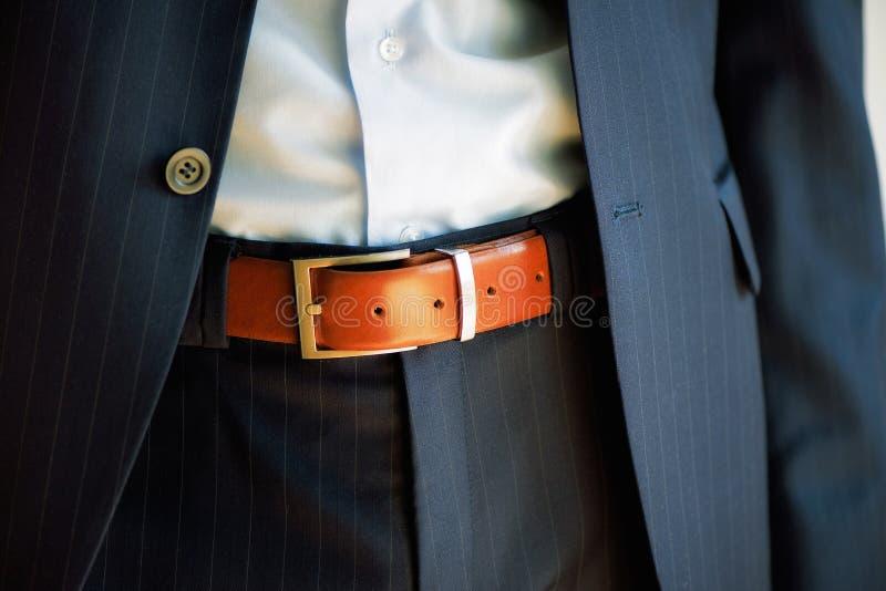 O homem veste a correia Homem de negócios novo no terno ocasional com acessórios Forma e conceito da roupa Noivo que prepara-se d imagem de stock royalty free