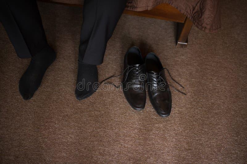 O homem veste sapatas Amarre os laços nas sapatas Estilo do ` s dos homens profissões Para preparar-se para o trabalho, à reunião fotos de stock