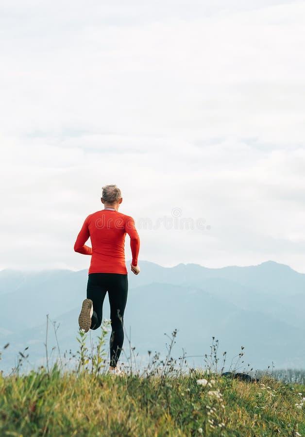 O homem vestido na camisa longa vermelha da luva corre pela estrada com o tiro vertical do fundo da montanha imagens de stock