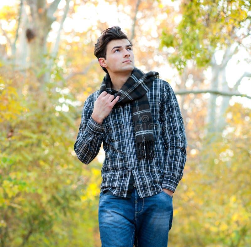 O homem vestiu-se em um lenço da manta que anda no parque do outono fotografia de stock royalty free