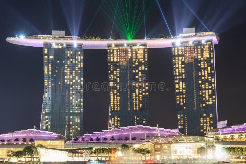 O hotel de Marina Bay Sands com luz e o laser mostram em Singapura fotografia de stock