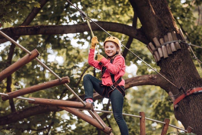 o o i 叫愉快的儿童的男孩,当爬高树和时 免版税图库摄影