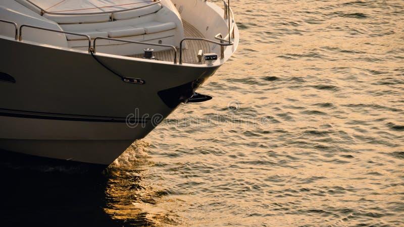 O iate está navegando no mar na hora dourada imagem de stock