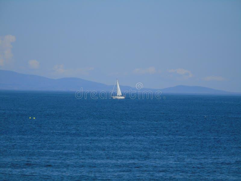 O iate solitário está para fora branco no mar azul fotografia de stock
