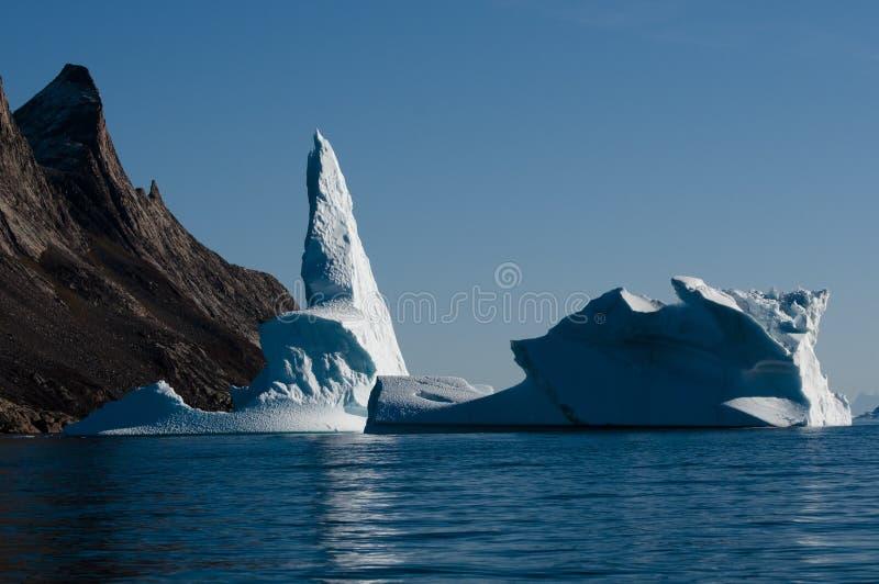 O iceberg imita a forma adjacente da montanha imagem de stock