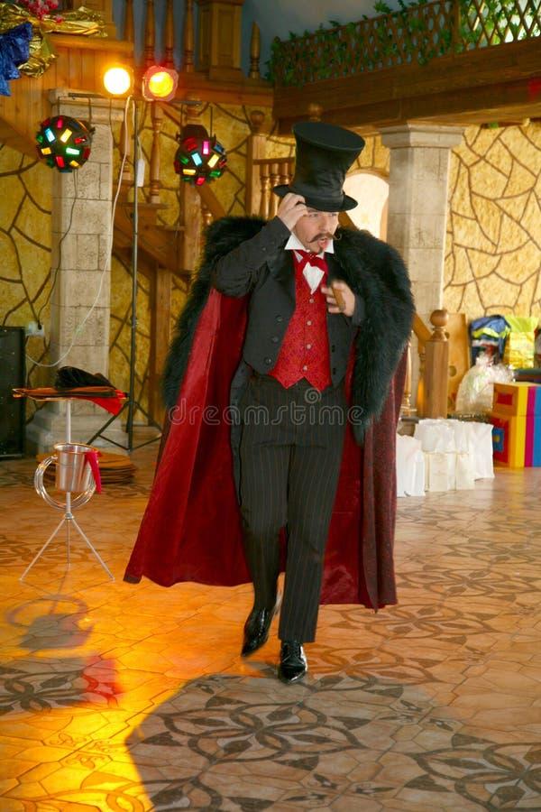 O ilusionista do mágico dos maestros mostra na cena do design de interiores imagens de stock royalty free