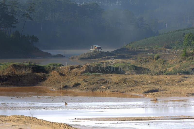 O impacto das alterações climáticas, feito terra seca, dos escassezs de água Casa pequena só entre a parte seca 2 dos rios foto de stock